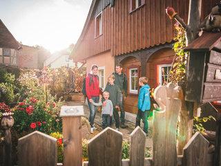Familie im Blumengarten vor Umgebindehaus